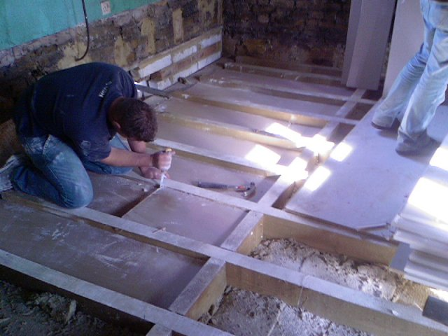 A man soundproofing the floor